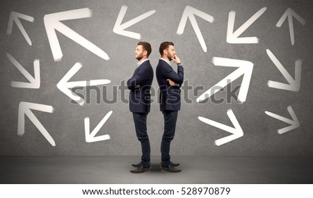 Young conflicted businessman choosing between two directions with arrows around him