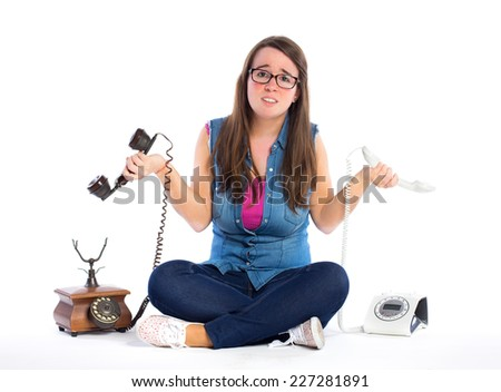 Young confused woman holding two telephones isolated on white background - stock photo