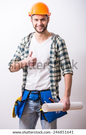 Young construction man with a project on building. - stock photo