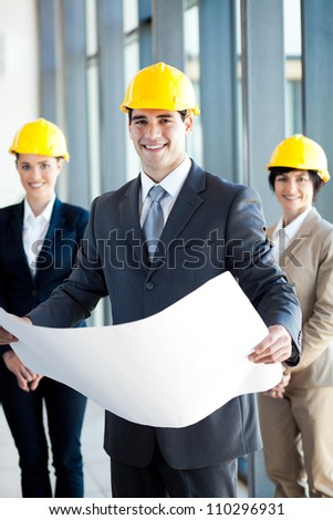 young construction manager holding blue print in front of colleagues - stock photo