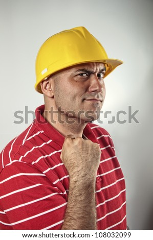 Young construction worker in red shirt wearing yellow hard hat safety equipment raising his fist. Conceptual image: confidence, power, determination; energy; winning; security. - stock photo