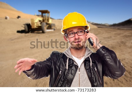 Young Construction Worker on Cell Phone in Dirt Field with Tractor in the Background.