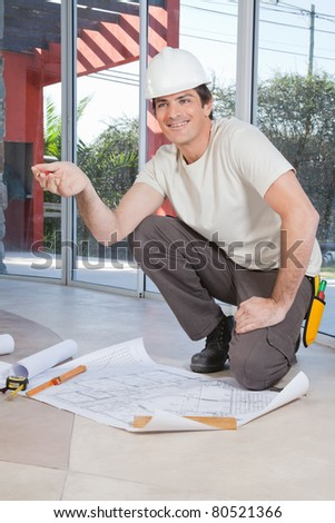 Young construction worker pleased with blueprint - stock photo