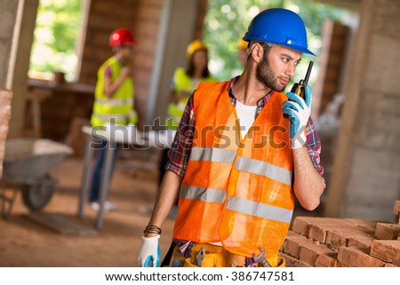 Young construction worker talking on walkie talkie at building site - stock photo