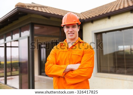 young construction worker with arms crossed in front of a house - stock photo