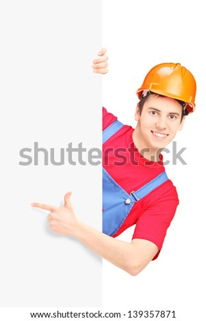 Young construction worker with helmet gesturing on a blank panel isolated on white background - stock photo