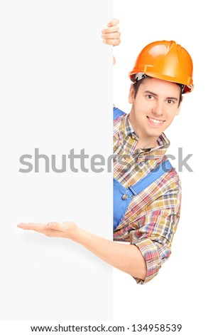 Young construction worker with helmet posing and gesturing on a panel isolated on white background - stock photo