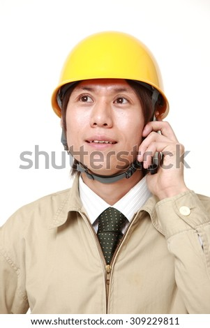 Young construction worker with smart phone