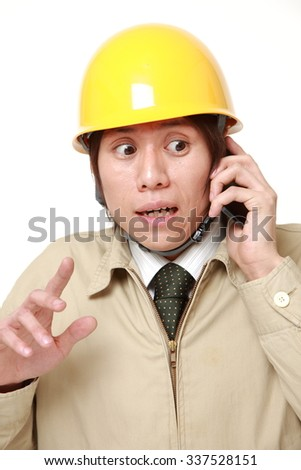 Young construction worker with smart phone shocked