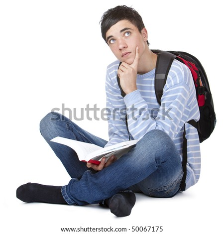 Young contemplative male student sitting on floor with book. Isolated on white. - stock photo