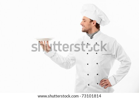 Young cook holding an empty plate on a white background - stock photo
