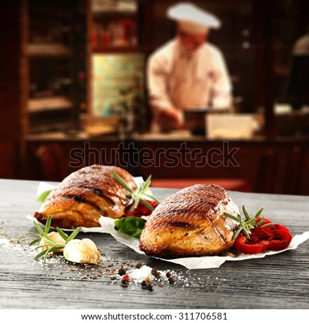 young cook in kitchen interior of bar and black space and duck meat  - stock photo