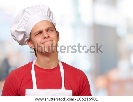 young cook man having an idea against an abstract background