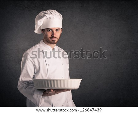 Young cook man with uniform carrying baking tin over grunge background. - stock photo