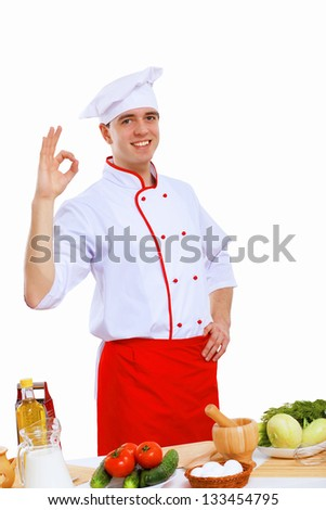 Young cook preparing food wearing a red apron - stock photo