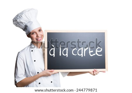 """young cook presenting a blackboard with the message """"� la carte"""" - stock photo"""