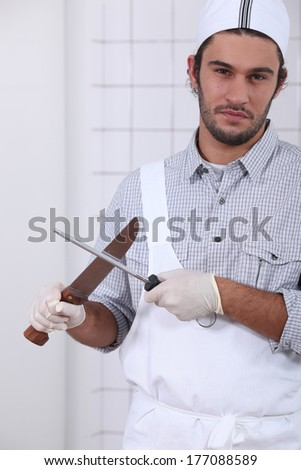 Young cook sharpening knives - stock photo