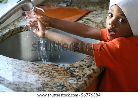 Young cook washing his hands in the kitchen sink. - stock photo