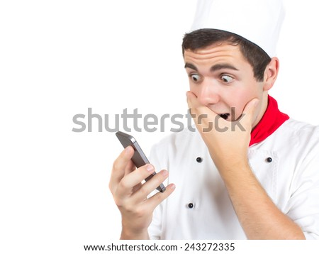Young Cook With Red Scarf Looking At Phone Surprised, Isolated On White - stock photo