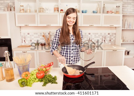 Young cooker frying meat on stove and making salad for breakfast - stock photo