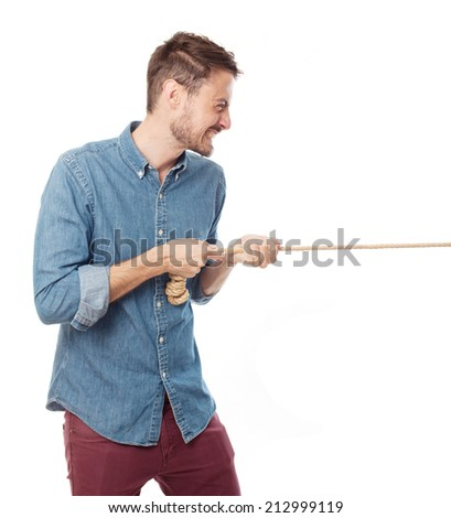 young cool man pulling a rope - stock photo