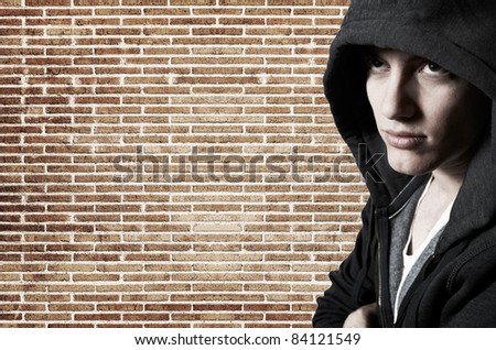 Young cool street style fashion male model posing at brick wall - stock photo