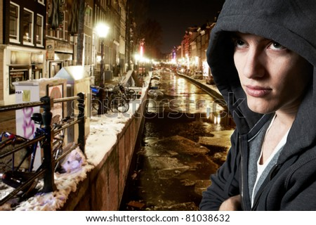 Young cool street style fashion male model posing in Amsterdam at night - stock photo