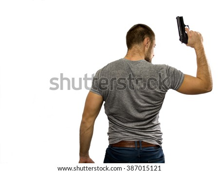 Young cop holding a gun in the right hand, seen from the back - stock photo