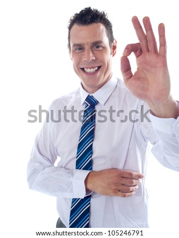 Young corporate associate gesturing excellent sign to camera - stock photo