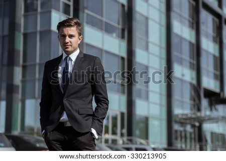 Young corporate manager posing in front of building - stock photo