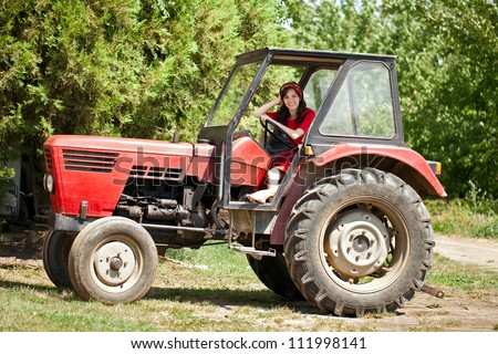 Young country girl on tractor, countryside