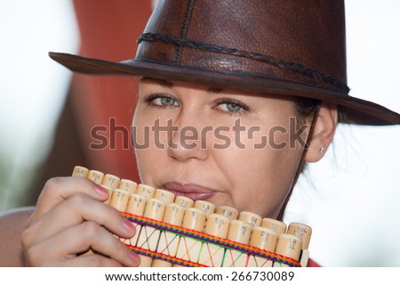 Young country woman in cowboy hat playing the panpipe - stock photo