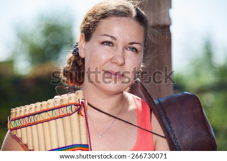Young country woman with cowboy hat with panpipe - stock photo