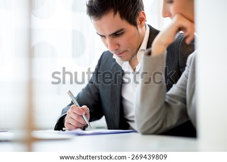 Young couple, a business man and woman, sitting in an office checking a document or contract before signing it. - stock photo