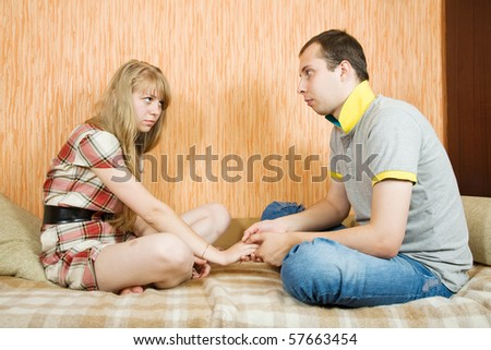 young couple after quarrel inside. Focus on girl only - stock photo
