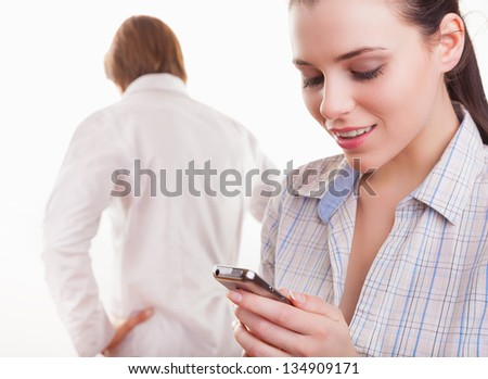 Young couple after quarrel. Woman looking with a smile on your phone in the foreground - stock photo