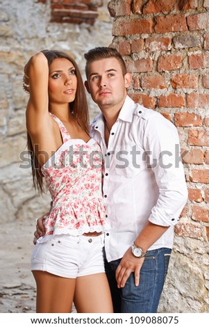 Young couple against a brick wall. - stock photo
