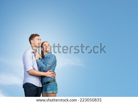 Young couple against sky background hugging each other