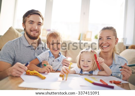Young couple and cute children drawing on weekend