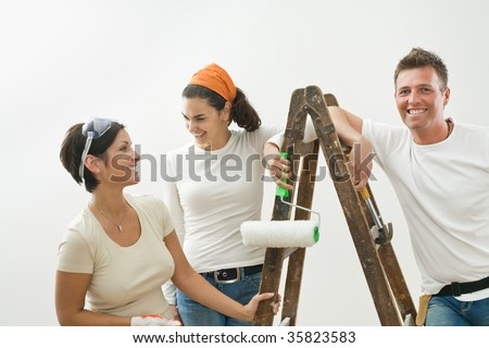 Young couple and friend painting new home, smiling.  Isolated on white background. - stock photo