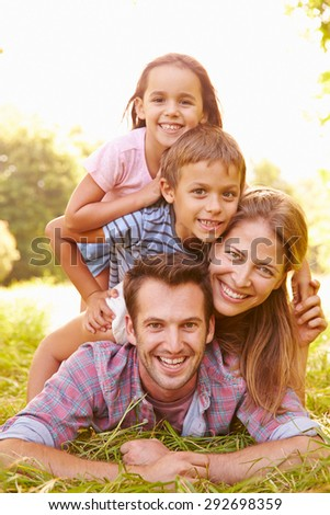 Young couple and kids having fun together outdoors - stock photo