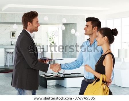 Young couple and real estate agent shaking hands, smiling. Side view. - stock photo
