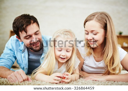 Young couple and their little daughter relaxing at home - stock photo