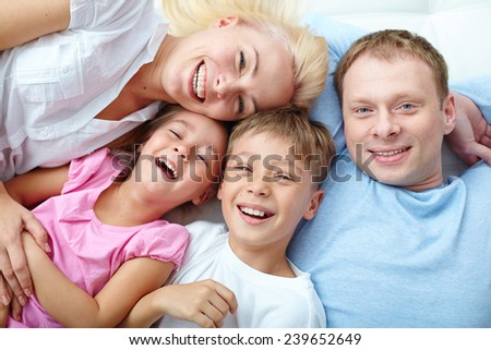 Young couple and two cute children laughing - stock photo