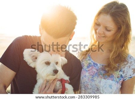 young couple and white dog happily together. couple taking a morning walk with their dog. concept about couples,animals and people - stock photo