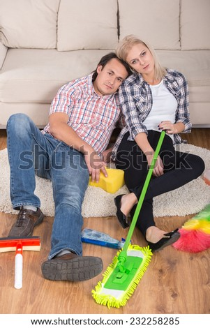 Young couple are sitting on the floor with cleaning products. Tired. - stock photo