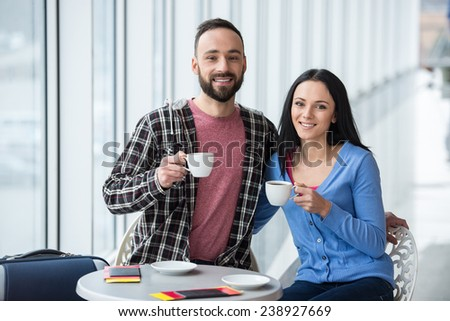 Young couple are  sitting with suitcase in international airport, are drinking coffee and looking at the camera. - stock photo
