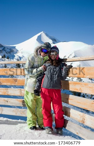 young couple are smiling in front of a beautiful winter background