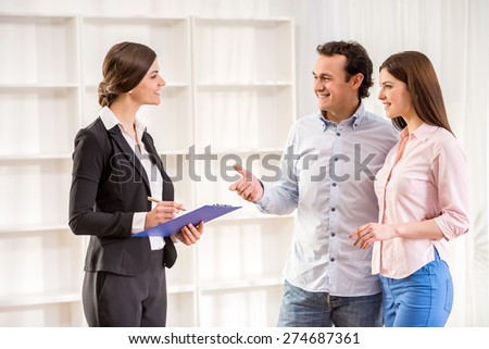 Young couple are talking to real estate agent. - stock photo