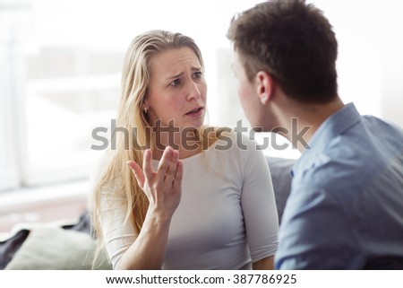 Young couple arguing in their living room. Portrait of blond young lady talking to her boyfriend.  - stock photo